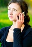 La muchacha habla por el teléfono móvil Fotos de archivo libres de regalías