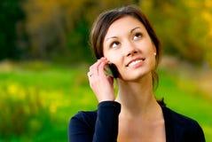 La muchacha habla por el teléfono móvil Foto de archivo
