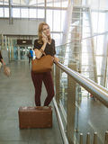 La muchacha habla por el teléfono y espera el vuelo en el aeropuerto Fotografía de archivo