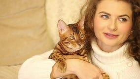 La muchacha habla y besando el gato de Bengala pet almacen de metraje de vídeo