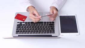 La muchacha hace compras en línea usando el cuaderno y el ordenador portátil en la oficina Diversas tarjetas de crédito Cierre pa metrajes