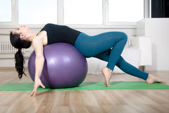 La muchacha hace ejercicios en una bola del gimnasio Fotografía de archivo libre de regalías