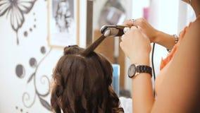 La muchacha hace el peinado en salón metrajes