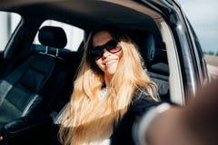 La muchacha hace el selfie que se sienta detrás de la rueda del coche Fotos de archivo libres de regalías