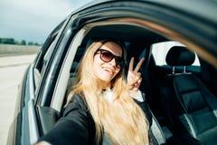La muchacha hace el selfie que se sienta detrás de la rueda del coche Fotografía de archivo libre de regalías