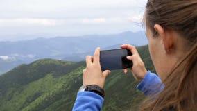 La muchacha hace la foto en el smartphone que se coloca en la montaña metrajes
