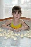La muchacha hace las bolas de masa hervida Fotografía de archivo