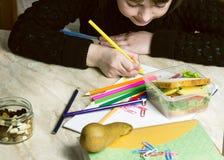 La muchacha hace las lecciones, en las mentiras de la tabla un bocadillo, fruta, nueces, libros de texto, lápices, bocadillo imágenes de archivo libres de regalías