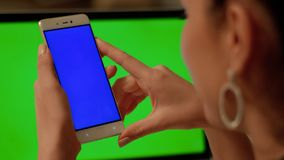 La muchacha hace la llamada video en el teléfono con la pantalla azul imágenes de archivo libres de regalías