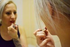 La muchacha hace maquillaje Imágenes de archivo libres de regalías