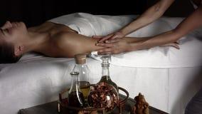 La muchacha hace masaje de relajaci?n con aceite almacen de metraje de vídeo