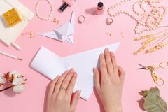La muchacha hace la papiroflexia de papel de la grúa Visión superior fotos de archivo