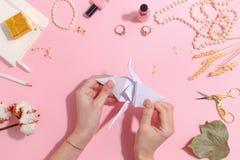 La muchacha hace la papiroflexia de papel de la grúa Visión superior fotos de archivo libres de regalías