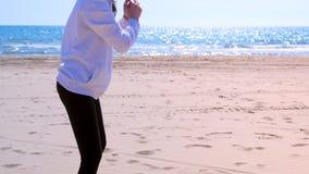 La muchacha hace posiciones en cuclillas en ejercicios del deporte al aire libre de la aptitud de la playa del arena de mar en el metrajes