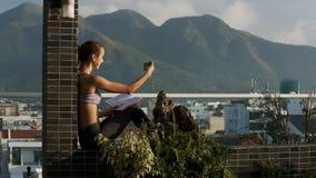 La muchacha hace Selfie que se sienta en terraza contra las colinas