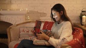 La muchacha hace un deseo y abre un paquete del regalo de la Navidad el concepto de días de fiesta y de Año Nuevo la muchacha es  almacen de metraje de vídeo