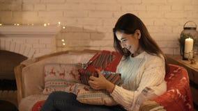 La muchacha hace un deseo y abre un paquete del regalo de la Navidad el concepto de días de fiesta y de Año Nuevo la muchacha es  almacen de video