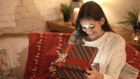 La muchacha hace un deseo y abre un paquete del regalo de la Navidad el concepto de días de fiesta y de Año Nuevo la muchacha es  metrajes