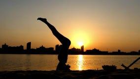 La muchacha hace un Headstand en la puesta del sol cerca del río almacen de video