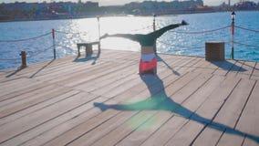La muchacha hace un Headstand en la puesta del sol cerca del mar almacen de video