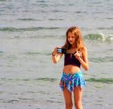 La muchacha hace un selfie en la playa del mar fotos de archivo