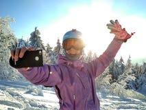 La muchacha hace un selfie en ropa del esquí en la montaña de la nieve fotos de archivo