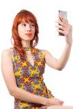 La muchacha hace un selfie Mujer joven del pelirrojo con el vestido del verano Imagenes de archivo