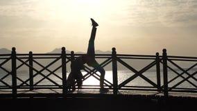 La muchacha hace una actitud del puente con la pierna aumentada contra el mar en la salida del sol, cámara lenta almacen de metraje de vídeo
