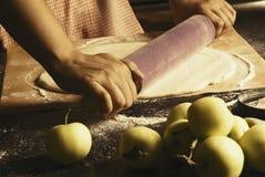 La muchacha hace una empanada de manzana Imagen de archivo libre de regalías