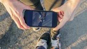 La muchacha hace una foto de zapatos por el teléfono Fotografía de archivo