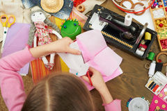 La muchacha hace una plantilla del vestido, visión superior, cosiendo los accesorios visión superior, lugar de trabajo de la cost Foto de archivo