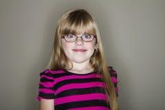 La muchacha hace una sonrisa de mirada linda pero divertida Imagenes de archivo