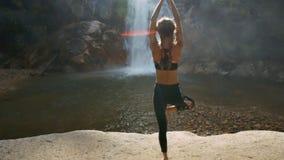 La muchacha hace yoga contra la cascada que cae en el lago