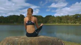 La muchacha hace yoga disfruta de paisaje cerca del río bajo Sun
