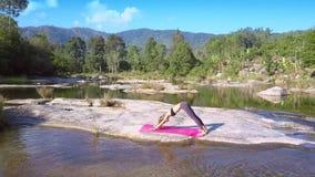La muchacha hace yoga en piedra plana entre el río ilustrado metrajes