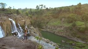 La muchacha hace yoga en tierra rocosa contra la cascada que fluye del acantilado almacen de video