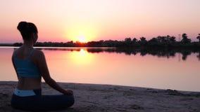 La muchacha hace yoga y mira la puesta del sol almacen de metraje de vídeo