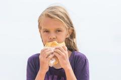 La muchacha hambrienta con un apetito mastica la torta deliciosa y mirado en el marco Imagen de archivo