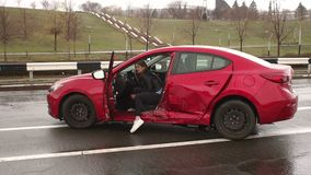 La muchacha herida se est? sentando en un coche quebrado despu?s de un accidente de tr?fico en un camino mojado metrajes