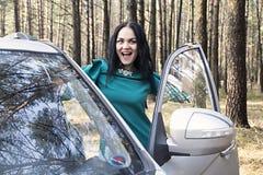 La muchacha hermosa abre la puerta de coche Imagen de archivo