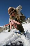 la muchacha hermosa activa con un snowboard chasquea la cámara Imagen de archivo