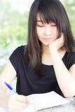 La muchacha hermosa adolescente del estudiante tailandés escribe un libro que se sienta en parque Imagen de archivo libre de regalías