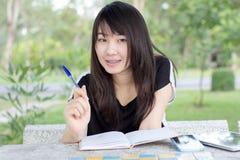 La muchacha hermosa adolescente del estudiante tailandés escribe un libro que se sienta en parque Imagen de archivo