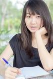 La muchacha hermosa adolescente del estudiante tailandés escribe un libro que se sienta en parque Fotografía de archivo