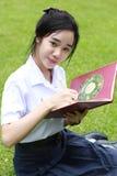 La muchacha hermosa adolescente del estudiante tailandés escribe un libro que se sienta en parque Imagenes de archivo