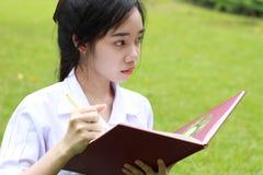 La muchacha hermosa adolescente del estudiante tailandés escribe un libro que se sienta en parque Fotografía de archivo libre de regalías
