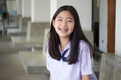 La muchacha hermosa adolescente del estudiante tailandés feliz y se relaja en escuela Imágenes de archivo libres de regalías