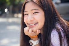 La muchacha hermosa adolescente del estudiante tailandés feliz y se relaja en escuela Fotografía de archivo