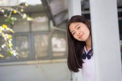 La muchacha hermosa adolescente del estudiante tailandés feliz y se relaja en escuela Imagen de archivo