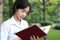 La muchacha hermosa adolescente del estudiante tailandés leyó un libro que se sentaba en parque Imágenes de archivo libres de regalías
